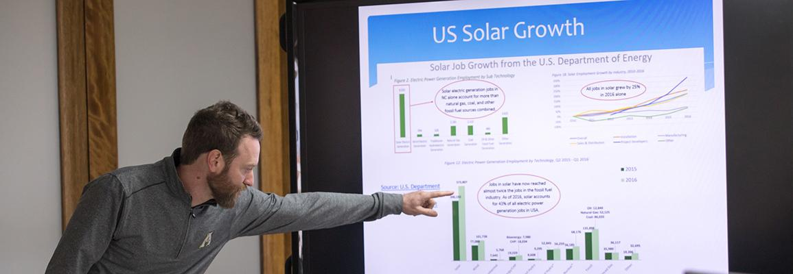 presenter discussing power point slide of a graph of solar growth